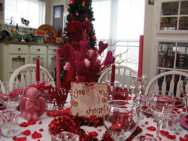 luxury-valentines-day-table-decoration_pink-angel-sculpture_red-candle_valentines-proverb_red-ribbon_glass-candle-holder_heart-shaped-ornament_pink-plate_romantic-ambiance_red-rose-petals-615x461